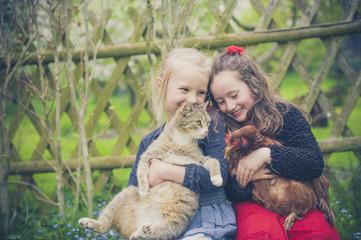 Portrait von zwei kleinen Mädchen mit Katze und Huhn