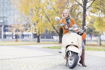 Polen, Warschau, Frau auf Motorroller
