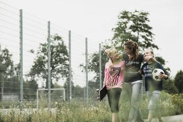 Drei glückliche Teenager-Mädchen mit Fußball und Skateboard-Seite an Seite