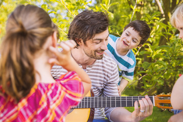 Vater mit Kindern, Gitarre spielen im Garten