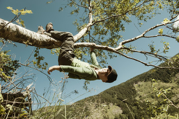 Junge hängt am Zweig eines Baumes
