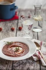 Tomatensuppe mit saurer Sahne, Thymian und ein Glas Wasser