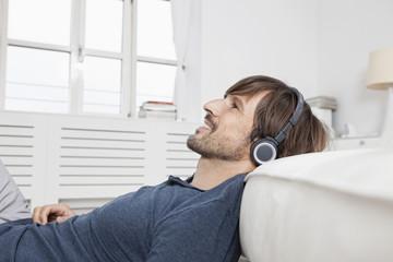 Mann sitzt auf dem Sofa, tragen Kopfhörer