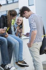Gruppe von Freunden im Freien mit Handys