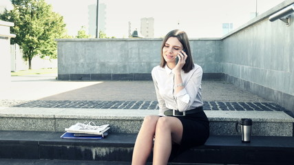 Businesswoman talking on cellphone while sitting on stairs in th