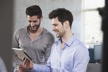 Zwei Kollegen mit Tablet-PC in einem offenen Großraumbüro
