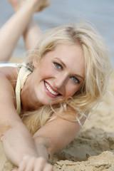Portrait einer glücklichen jungen Frau, die am Strand liegt