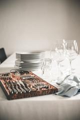Tisch mit Stapel Tellern, Wein und Wasser-Gläser und Besteckschublade