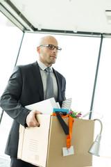 Geschäftsmann trägt Karton ins neue Büro