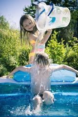 Mädchen spritzt Wasser auf Bruder