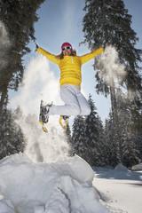 Österreich, Salzburger Land, Altenmarkt-Zauchensee, Frau mit Schneeschuhen springt in der Winterlandschaft