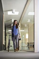 Geschäftsfrau, Ankunft im Büro mit Rennrad