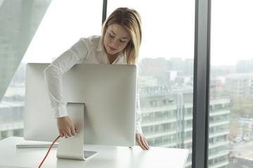 Geschäftsfrau verbindet Computer-Monitor