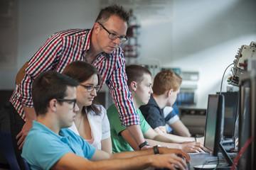 Berufsschüler mit Lehrer im Computerlabor
