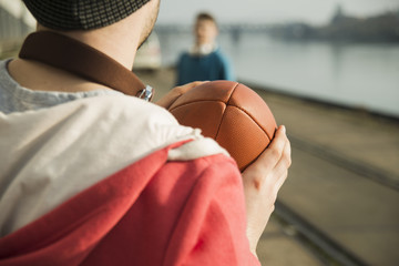 Junger Mann und Teenager spielen Fußball am Flussufer
