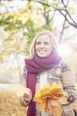 Polen, Warschau, Blonde Frau im Herbstlaub