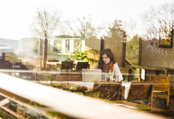 Junge Frau mit Notebook im Café, Blick von außen