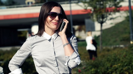 Young attractive businesswoman talking on cellphone in the city