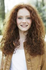Lächelndes Mädchen mit lockigen roten Haaren