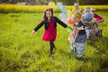 Drei Kinder in Bewegung, mit Holzwagen und Luftballons