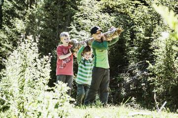 Drei Jungen mit Baumstamm in der Natur