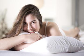 Lächelnde junge Frau mit Kissen auf dem Bett liegend