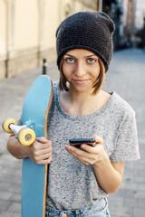 Junge Skateboarderin hält Smartphone und Skateboard