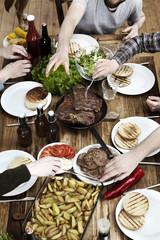 Freunde essen Kartoffeln, Steaks und Frikadellen auf Holztisch