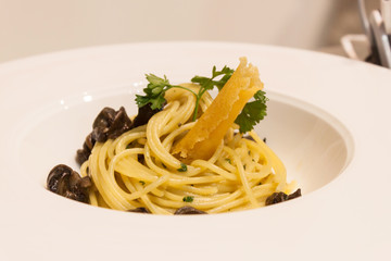 Spaghetti with snails and sauce in a dish