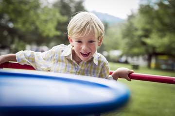 Lächelnde kleine Jungen auf einem Karussell auf Spielplatz