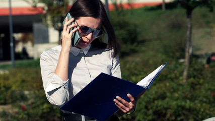 Businesswoman talking on cellphone and reading documents in the