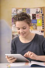 Weibliche Schüler machen Hausaufgaben mit Tablet-PC