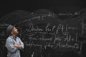Mann liest Text auf Tafel