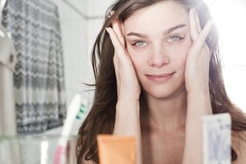 Jungen Frau schaut auf ihr Spiegelbild im Bad