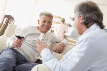 Reifer Mann trinkt Rotwein mit seinem besten Freund im Wohnzimmer