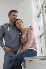 Paar umarmt sich am Fenster