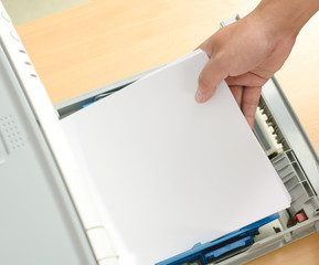 Male hand holding paper sheets into printer tray in office.