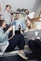 Gruppe kreativer Profis auf Treppe mit Bierchen