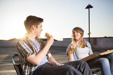 Glücklicher Teenager, Essen und Trinken auf Parkplatz