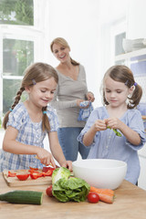 Mädchen schneidet Gemüse in der Küche, Mutter steht im Hintergrund
