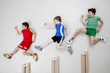 Jungen springen über Hürden
