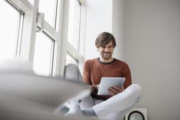 Tablet-PC, sitzt auf der Fensterbank