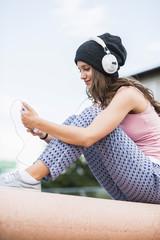 Lächelndes Teenager-Mädchen mit Smartphone hört Musik mit Kopfhörern