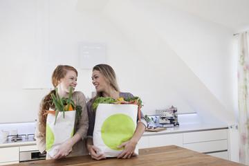 Zwei Frauen mit Einkaufstaschen und Einkäufen
