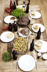 Gericht mit Kartoffeln, Steaks und Frikadellen auf Holztisch