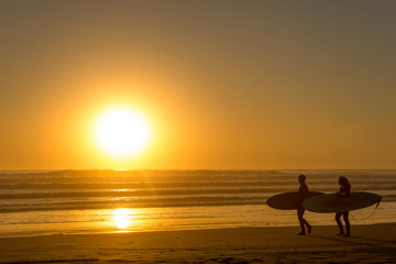 surfers walking on the beach in the sunset