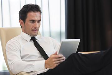 Geschäftsmann mit Tablet-Computer im Hotelzimmer