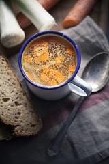 Hausgemachte Hühnerbrühe in der Tasse mit Brotscheiben und Zutaten