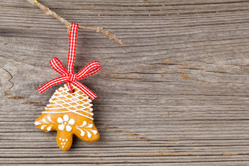 Gingerbread cookie hanging on wooden background. Christmas decor