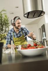 Junger Mann mit Kopfhörern in der Küche kocht zu Hause